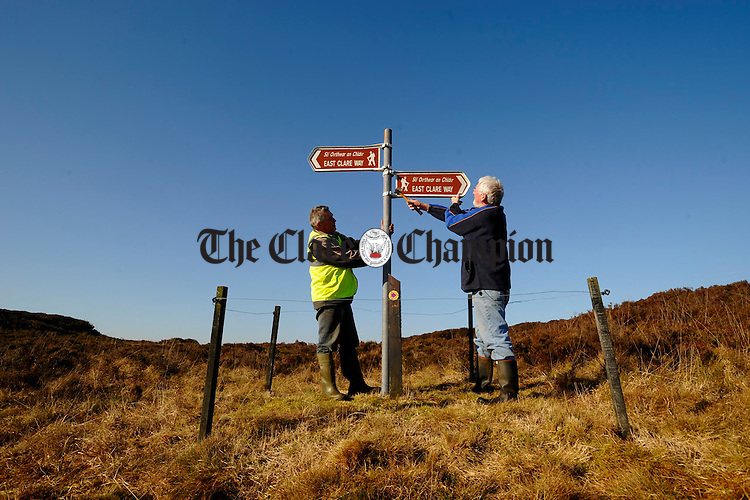John Mc Guinness and Michael Collins put the finishing touches to new East Clare Way signage during works as part of the Feakle Rural Social Scheme on top of Ballycroum mountain in Feakle. Photograph by John Kelly.