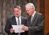 """United States Senators Gary Peters (Democrat of Michigan), left, and Ron Johnson (Republican of Wisconsin), right, look over a document prior to hearing testimony before the United States Senate Committee on Homeland Security & Governmental Affairs during a hearing entitled """"Examining CMS's Efforts to Fight Medicaid Fraud and Overpayments"""" on Capitol Hill in Washington, DC on Tuesday, August 21, 2018.<br /> Credit: Ron Sachs / CNP"""