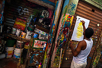 """A Colombian sign painter writes with a brush while working on a music party poster in the sign painting workshop in Cartagena, Colombia, 12 December 2017. Hidden in the dark, narrow alleys of Bazurto market, a group of dozen young men gathered around José Corredor (""""Runner""""), the master painter, produce every day hundreds of hand-painted posters. Although the vast majority of the production is designed for a cheap visual promotion of popular Champeta music parties, held every weekend around the city, Runner and his apprentices also create other graphic design artworks, based on brush lettering technique. Using simple brushes and bright paints, the artisanal workshop keeps the traditional sign painting art alive."""