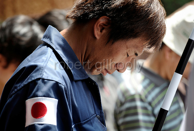 A Japanese nationalist man bows in prayer during a minute's silence held to commemorate the end of World War II at Yasukuni Shrine in Tokyo, Japan on 15 Aug. 2008. Wartime prime minister Hideki Tojo - who ordered the attack on Peal Harbor and was charged and hanged as a war criminal after World War II, is enshrined inside the controversial Yasukuni Shrine together with 13 other convicted war criminals, a fact that still angers citizens in China and South Korea, both of which fell vicim to Japan's wartime activities. Aug 15. is the anniversary of Japan's surrender in World War II and 100s of thousands of pilgrims from around the country visit the shrine...Photographer: Robert Gilhooly