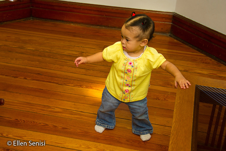 MR / Schenectady, NY. Infant in early walking stage (girl, 11 months, African American & Caucasian) exhibits 11-month-old human development milestone behavior as she cruises while holding onto furniture. MR: Dal4. ID: AL-HD. © Ellen B. Senisi