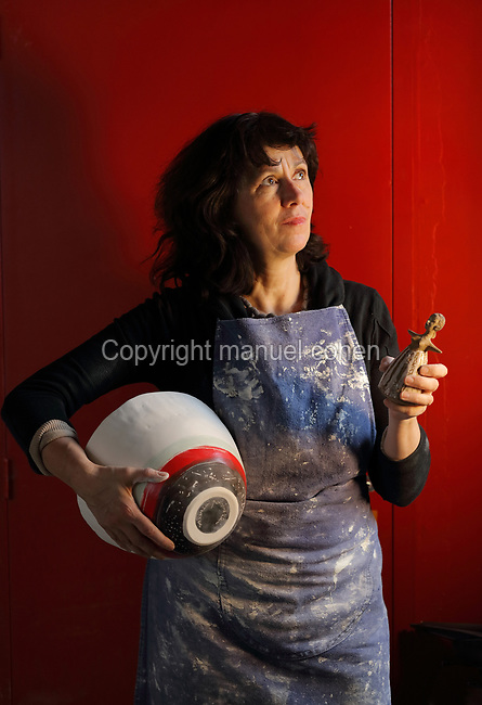 Ceramicist Valeria Polsinelli holding a bowl and a female figurine, photographed in 2017 in her studio in Montreuil, a suburb of Paris, France. Polsinelli creates everyday vessels, water jugs, jewellery and figurines and stoppers of female busts, with features and hairstyles from various world cultures. Picture by Manuel Cohen