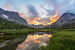 Wind River Range, WY: A colorful sunset and reflections in the North Fork of the Popo Agie River with the profile of the Cirque of the Towers and Lizard Head in the distance; Popo Agie Wilderness in the Bridger National Forest in summer