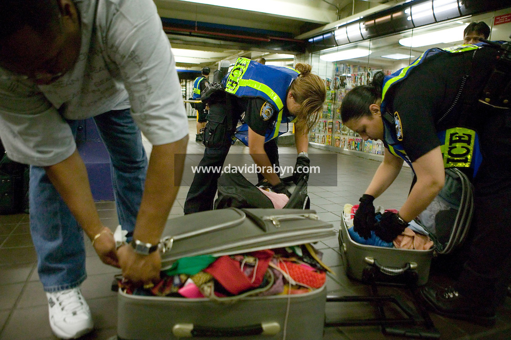 22 July 2005 - New York City, USA - Police officer Rosa Medina (R) and Nixaliz Gerena (C) search bags of a man (L) about to enter the 42 St Port Authority Bus Terminal subway station, 22 July 2005, New York City, USA. The NYPD decided to subject riders to random bag inspections following the second attack on London's transit system in two weeks. Photo Credit: David Brabyn.