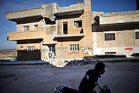 SYRIA, 02.2012, Idlib, Idlib province. © Timo Vogt/EST&OST. A man on a motorcycle driving past a shelled residential house in the outskirts.