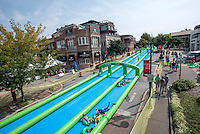 NWA Democrat-Gazette/J.T. WAMPLER Several thousand people turned out for a 1,000 foot long water slide on Dickson St. in Fayetteville Sunday August 30, 2015. The water slide was brought to Fayetteville by Slide the City, a company based in Salt Lake City. Part of the event's proceeds will benefit Soldier On Service Dogs, a nonprofit organization that raises, trains and gives away service dogs to veterans who have post-traumatic stress disorder or traumatic brain injuries. For more photos of the event go to http://nwamedia.photoshelter.com/