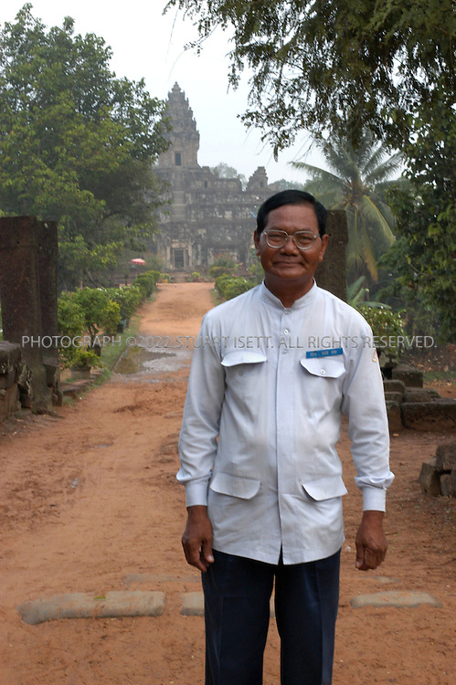 4/20/2003--Angkor Wat Temples, Siem Reap, Cambodia ..BAKONG, Roluos Group. Ticket inspector..Bakong is located at Roluos south of Prak Ko.It was build in late ninth century (881) by king Indravarman I dedicated to Siva (Hindu) followed Prah Ko art style. ...BACKGROUND .Bakong was the center of the town of Hariharalaya, a name derived from the god Hari-Hara; a synthesis of Siva and Visnu. It is a temple representing the cosmic Mount Meru. Four levels leading to the Central Sanctuary correspond to the worlds of mythical beings (Nagas, Garudas, Raksasas and Yaksas)...All photographs ©2003 Stuart Isett.All rights reserved.This image may not be reproduced without expressed written permission from Stuart Isett.
