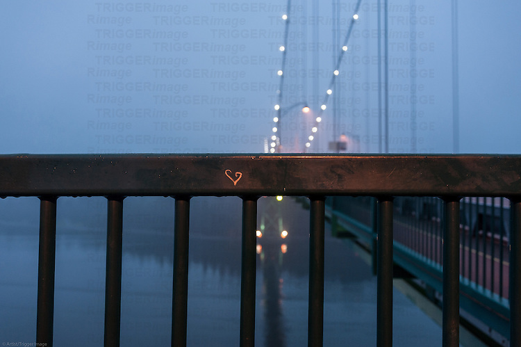 A heart etched onto the railing of a bridge in the fog.