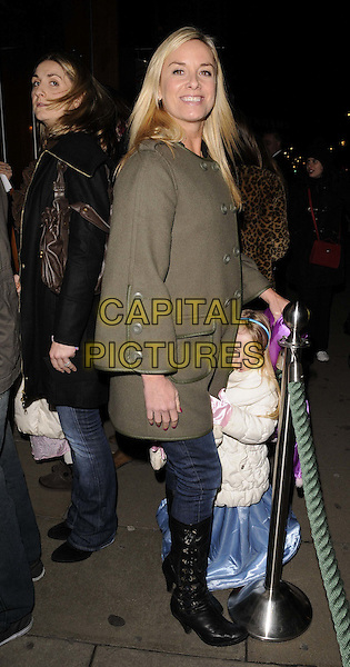 Tamzin Outhwaite & her daughter.The Disney Year Of The Princess launch party, The Disney Store, Oxford St., London, England..January 25th, 2012.full length black boots jean denim green side hiding jacket coat holding leg kid child mother mom mum family.CAP/CAN.©Can Nguyen/Capital Pictures.