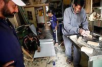Syria, Deir az-Zor, 2013/03/23..A neighbourhood initiative works in a little carpentry workshop and recycles former wooden sticks from pro-Assad banners to stretchers and brackets in order to give it for free to those who need it in Deir az-Zor. .Syrie, Deir ez-Zor, 23/03/2013.Des habitants du quartier travaillent dans un petit atelier de menuiserie et recyclent le bois des anciennes bannières à la gloire d'al-Assad afin de confectionner gratuitement des brancards et des béquilles pour ceux qui en ont besoin à Deir ez-Zor..Photo: Timo Vogt / Est&Ost Photography.
