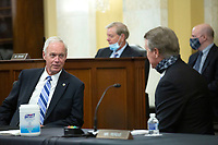 United States Senator Ron Johnson (Republican of Wisconsin) speaks to United States Senator David Perdue (Republican of Georgia) during a United States Senate Committee on the Budget business meeting at the United States Capitol in Washington D.C., U.S., on Thursday, June 11, 2020, as they consider the nomination of Director, Office of Management and Budget (OMB) Russell Vought to be White House Office of Management and Budget.  Credit: Stefani Reynolds / CNP/AdMedia