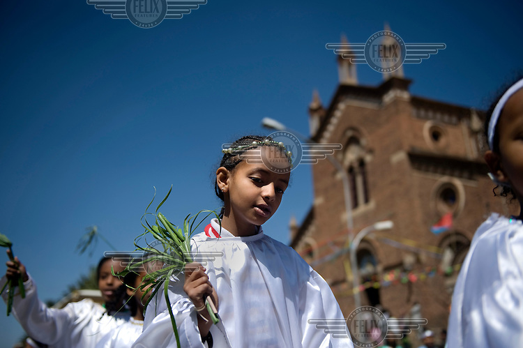 Children in white robes walk in a procession in front of St Joseph's Catholic Cathedral .