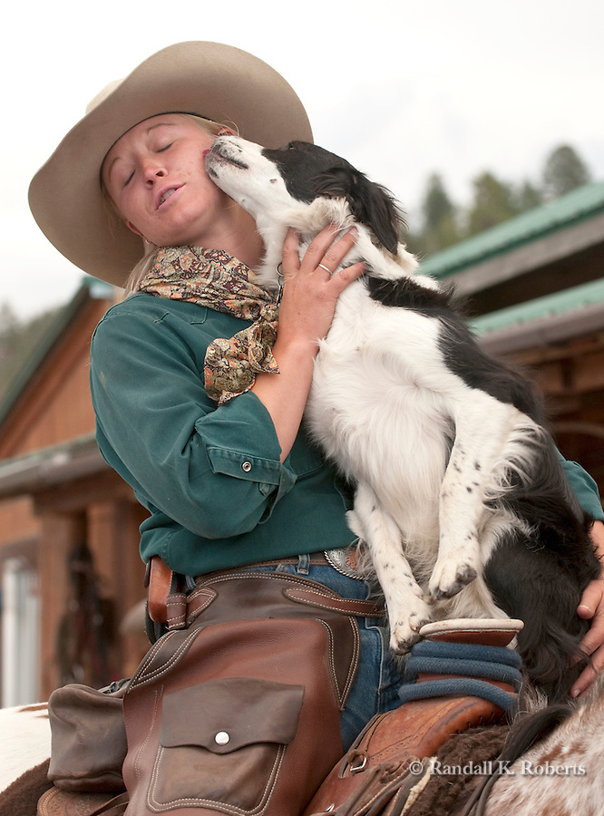 Chance the ranch dog gives wrangler Jesi DeVries some love at the Triangle X Wranch, Grand Teton National Park, Wyoming