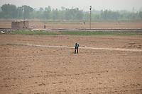 A daytime landscape view of a man working in a field near Dàtóng Shì Chéng Qū in Shānxī Province, China  © LAN