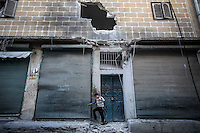 In this Sunday, Dec. 02, 2012 photo, a Syria child walks among the debris from a bakery's destroyed front after it was hit by one mortar shell killing four and injuring another two in Hullok district during heavy shelling in Aleppo, the Syrian's largest city. (AP Photo/Narciso Contreras)