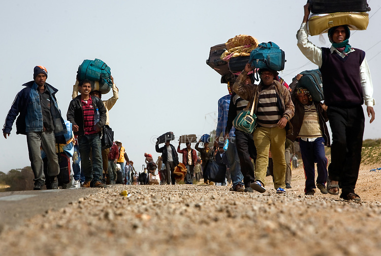 Thousands of Bangladeshi migrant workers walk 10 km to a refugee camp near the Tunisian side of the Ras Jidir border crossing with Libya, March 4, 2011. The border crossing is bursting, with many more refugees entering Tunisia than can be moved to the temporary shelters provided at the camp. More than half of the 180,000 people estimated to have fled Libya have crossed into Tunisia. Egyptian, Bangladeshi and Sri Lankan migrant workers are stuck at the border as aid organizations and governments struggle to get them home via an airlift operation.