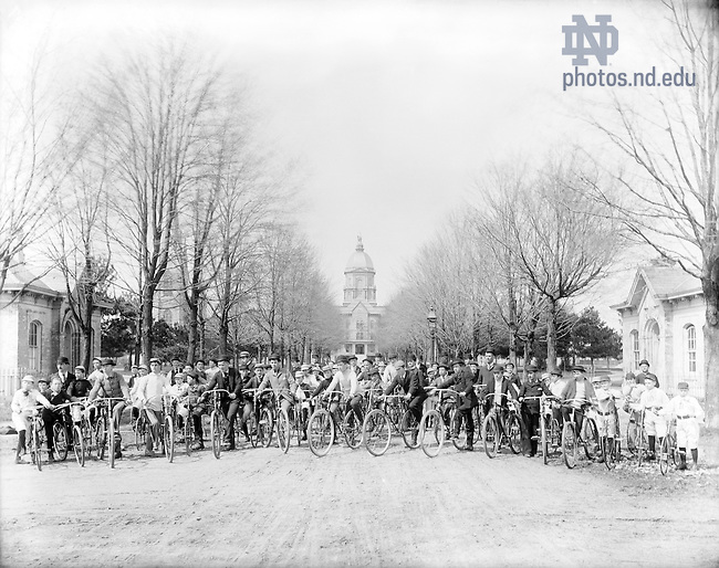 "GGPN 15/04:  A group of minim students with bicycles on Main Quad with Main Building in the background, Porter House to the left, and the Post Office to the right, c1890s..Caption:  ""Bicycle Army.""  Image from the University of Notre Dame Archives."
