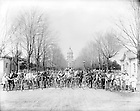 """GGPN 15/04:  A group of minim students with bicycles on Main Quad with Main Building in the background, Porter House to the left, and the Post Office to the right, c1890s..Caption:  """"Bicycle Army.""""  Image from the University of Notre Dame Archives."""