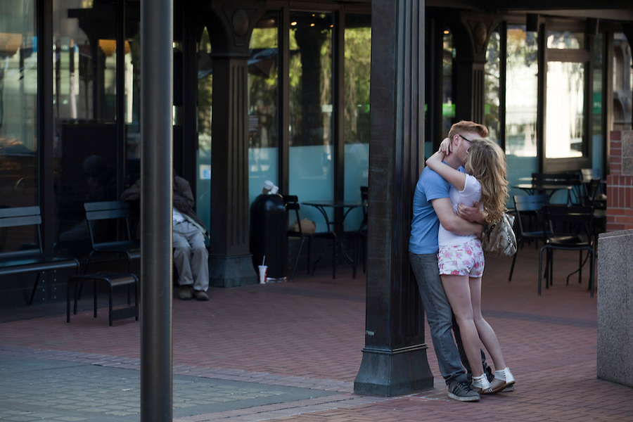 """A couple kiss in """"Pioneer Square"""" in downtown in Portland, Oregon on Wednesday,  April 24, 2013. Confidence among consumers fell in April to a nine-month low as Americans grew more pessimistic about the outlook for the economy. Photographer: Natalie Behring/Bloomberg News"""