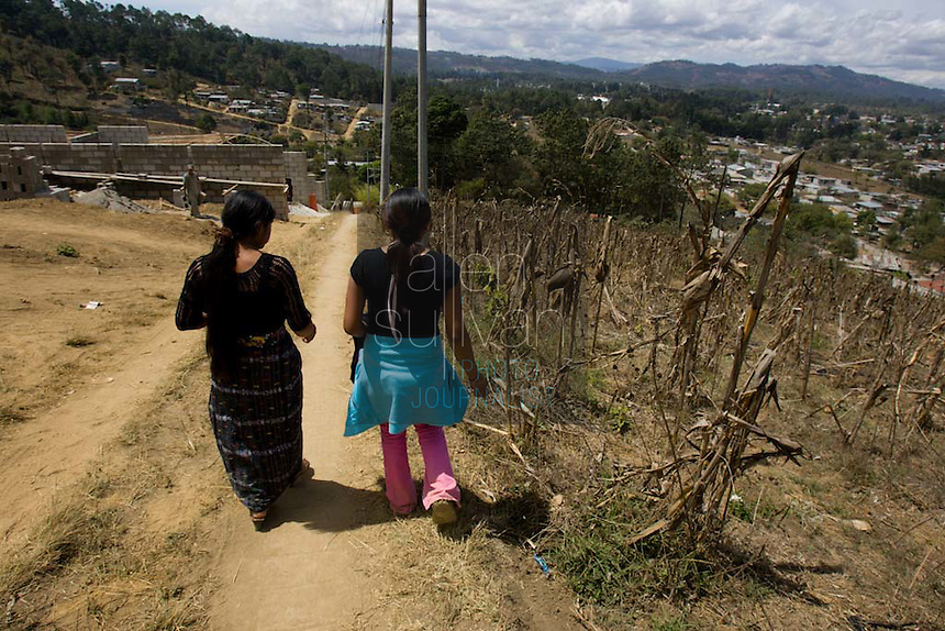 Maria (left), 16, and her friend, Alma de Los Angeles Sambrano Montufa, 15, walk in Alma's neighborhood in Chimaltenango, Guatemala on Thursday, March 8, 2007. Maria works at Legumex, a vegetable and fruit company that exports to the United States. She injured her wrist on the job and couldn't work today. Alma recently quit the company after a year and a half.