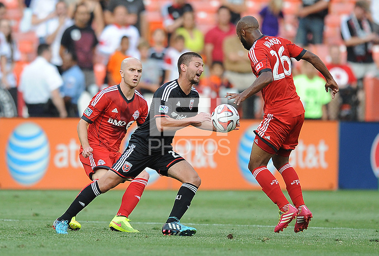 Washington D.C. - July 30, 2014:  Perry Kitchen (23) of D.C. United goes against Collen Warner and Michael Bradley (4) of Toronto FC. D.C. United defeated the Toronto FC 3-1 during a Major League Soccer match for the 2014 season at RFK Stadium.