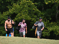 NWA Democrat-Gazette/J.T. WAMPLER Owner Brian Richardson (FROM THE RIGHT) walks up the second fairway with Hunter Wright and Marshall Ward Wednesday July 31, 2019 at Cedar Creek Disc Golf Course in rural Washington County near West Fork. For information about the course visit www.cedarcreekdgc.com/