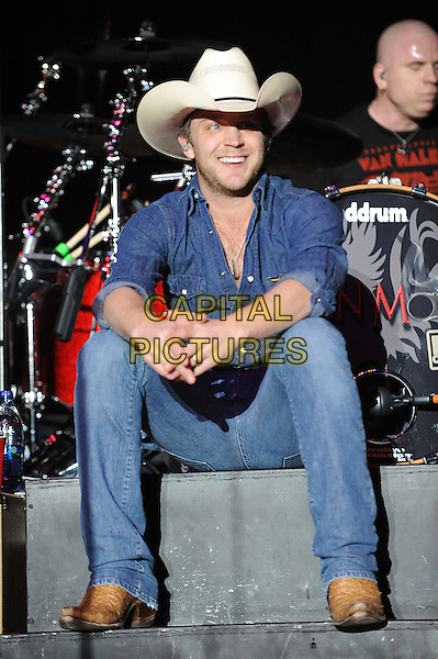 JUSTIN MOORE.Singer Justin Moore performs live at the 2011 Winterblast at the Hampton Coliseum, Hampton, Virginia, USA,  .29th January 2011..full length country music stage gig jeans shirt denim double cowboy hat sitting .CAP/ADM/MOO.© Moose/AdMedia/Capital Pictures.