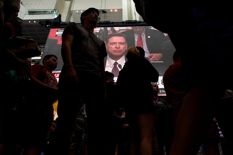 UNITED STATES - JUNE 8: Former FBI Director James Comey is shown testifying on the Newseum's large video screen during the Senate Select Intelligence Committee hearing as school groups pass by on Thursday, June 8, 2017. (Photo By Bill Clark/CQ Roll Call)