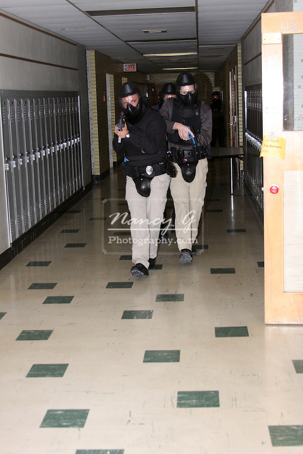 Male police officers in training holding a paint ball simulated gun clearing a school shooting scenario
