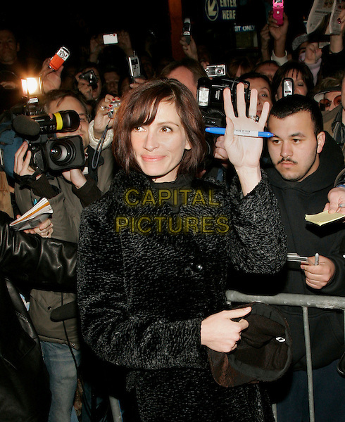 "JULIA ROBERTS.Signs autographs outside the location where her Broadway show ""Three Days of Rain""  is performing, New York, NY, USA..March 28th, 2006.Photo: Jackson Lee/Admedia/Capital Pictures.Ref: JL/ADM.half length black coat pen hand waving gesture palm fans photographers.www.capitalpictures.com.sales@capitalpictures.com.© Capital Pictures."