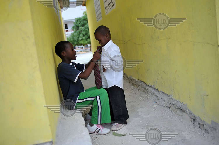 Boy at the Ebenezer Foundation Orphanage in Croix Besbouquets tie each others ties for Sunday mass. The orphanage is run by the Global Orphan Project. .Many children were orphaned when an 7.0 magnitude earthquake struck Haiti on 12/01/2010. Early reports indicated that more than 100,000 may have been killed and three million affected.