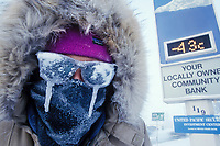 Man with icicles on glasses huddles under the outdoor temperature sign which reads a chilly minus 43 degrees in downtown Fairbanks, Alaska