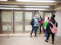 "Commuters and other travelers pass through the newly opened World Trade Center connecting passageway in New York on Monday, December 19, 2016. The passage, which connects the Chambers Street subway station with the WTC Oculus and further on the PATH station, is a vestige from the original World Trade Center, destroyed in the terrorist attack on Sept. 11, 2001. The ramp and the travertine flooring are original as well as a commemorative door, labeled ""MATF1 9-13"" indicating the area was searched by the Massachusetts Task Force 1 Urban Search and Rescue Team on September 13. (© Richard B. Levine)"