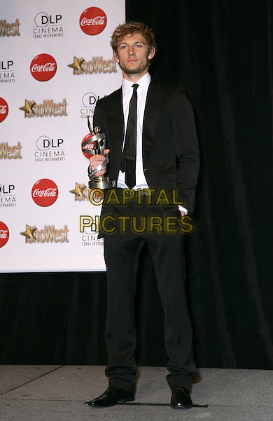 ALEX PETTYFER .SHOWEST Final Night Talent Awards at the Paris Resort Hotel and Casino,  Las Vegas, Nevada , USA,.18th March 2010..full length black suit tie hand in pocket white shirt award winner trophy .CAP/ADM/MJT.© MJT/AdMedia/Capital Pictures.