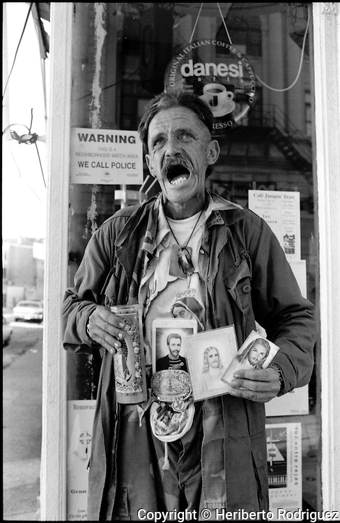 A homeless Mexican holds candles as he screams in front of Jumping Bean Cafe in the west side of Chicago Illinois. Photo by Heriberto Rodriguez