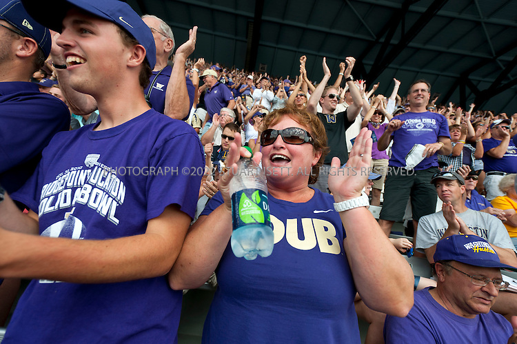 9/24/2011--Seattle, WA, USA...Lisa Kittilsby and her son Eric (left), watch a UW football game at Husky Stadium after a morning of tailgating on her yacht the Big Dawg,..The 'Big Dawg', owned by Lisa and Tim Kittilsby, is the biggest, most prominent boat that attends regular boat tailgate parties on docks near the UW (University of Washington) Husky Stadium. Up to 500 boats will tie up outside Husky Stadium on football game days, ranging from from small boats to huge yachts. The Big Dawg is a 92-foot, two-story yacht that dominates the tailgate parties...The tradition started when Lisa and Tim Kittilsby's parents, Frank and Jeanie Miles, took a 23-foot boat called The Mixer to a game over 40 years ago...©2011 Stuart Isett. All rights reserved.