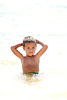 Small boy with hands placed on the back of his head relaxes in the water. Backlit shot creates washed out background. Strong midday sun reflects off the water.