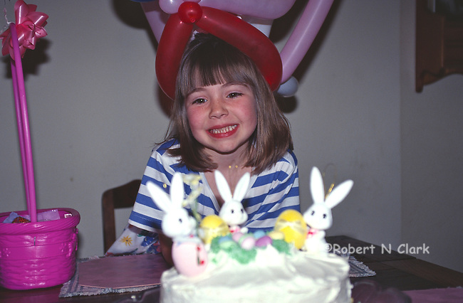 Girl with balloon hat and Easter cake