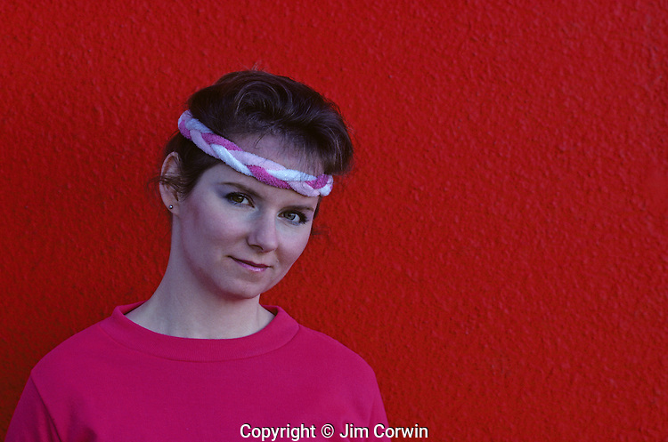 Young woman wearing head band portrait in front of red wall