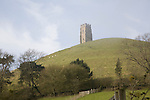 St Michael's Tower on Glastonbury Tor, Somerset, England in misty haze with blue sky.