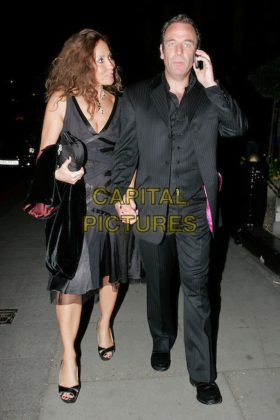 VANYA GREEN & ROBSON GREEN.Leaving the Royal Television Society Awards at the Grosvenor House Hotel, Park Lane, London, England..March 17th, 2009.rts full length black pinstripe suit dress holding hands talking on mobile phone couple .CAP/AH.©Adam Houghton/Capital Pictures.