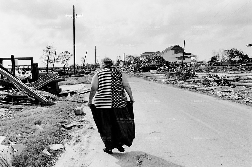 USA. Louisiana. Slidell. Aftermath of hurricane Katrina. Marina area near the lake Pontchartrain is virtually destroyed . Most houses were  destroyed by the storm, the tidal surge (water wave) and the floods. A woman, wearing a dress with the american flag, walks on the road  near the houses' ruins. The area is now empty and all its inhabitants have left away. The people could no longer and ever live again in the houses. The entire area needs to be bulldozed before any new construction can be built. Household waste. Destruction of the urban american way of life. © 2005 Didier Ruef