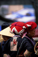 Red Zao women with intricately detailed head coverings and embroidered tunics at Sapa market, Sapa, Vietnam