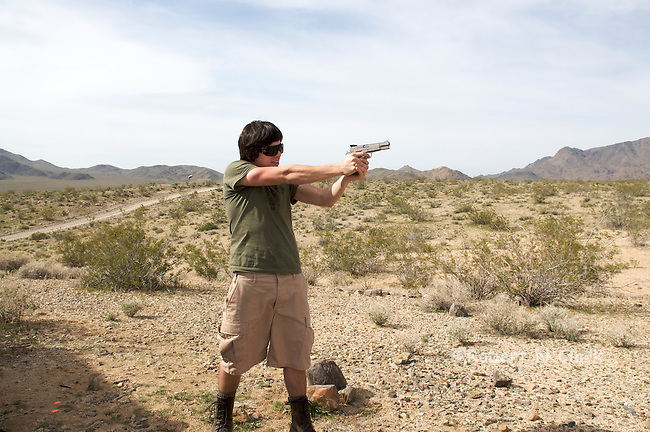 Youth firing Browning 9mm Hi Power semi-auto pistol