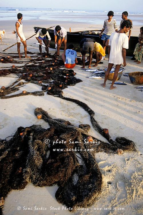 Men preparing their fishing nets at dawn, Colva Beach, Goa, India.