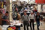 A picture taken on May 15, 2018 shows Palestinians shop at a market during the holy month of Ramadan, in the West Bank city of Nablus. Ramadan is sacred to Muslims because it is during that month that tradition says the Koran was revealed to the Prophet Mohammed. The fast is one of the five main religious obligations under Islam. Muslims around the world will mark the month, during which believers abstain from eating, drinking, smoking and having sex from dawn until sunset. Photo by Ayman Ameen