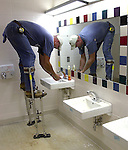Jack Roberson wears stilts into the boys bathroom as he takes a break from drop-ceiling installation at the newly constructed Cedar Hill Elementary School in Ardmore, Ala., in 2002.
