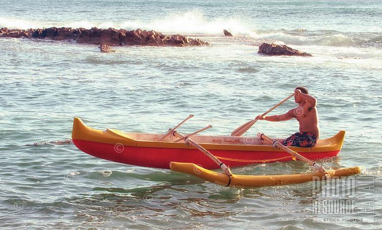 A Hawaiian man paddles an outrigger canoe off the coast of O'ahu.