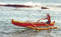 A Hawaiian man paddles an outrigger canoe off the coast of O'ahu.