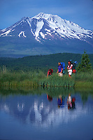 Mother, son and daughter backpacking near lake with Mt. Shasta in background, California